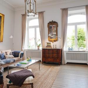 Piękny stylowy salon przenosi w czasie do minionej epoki. Na tle delikatnych odcieni brązu i beżu, wyrazistszym akcentem są pozłacane ramy lustra i wielkoformatowego obrazu powieszonego nad kanapą. Fot. Alvhem Makleri.