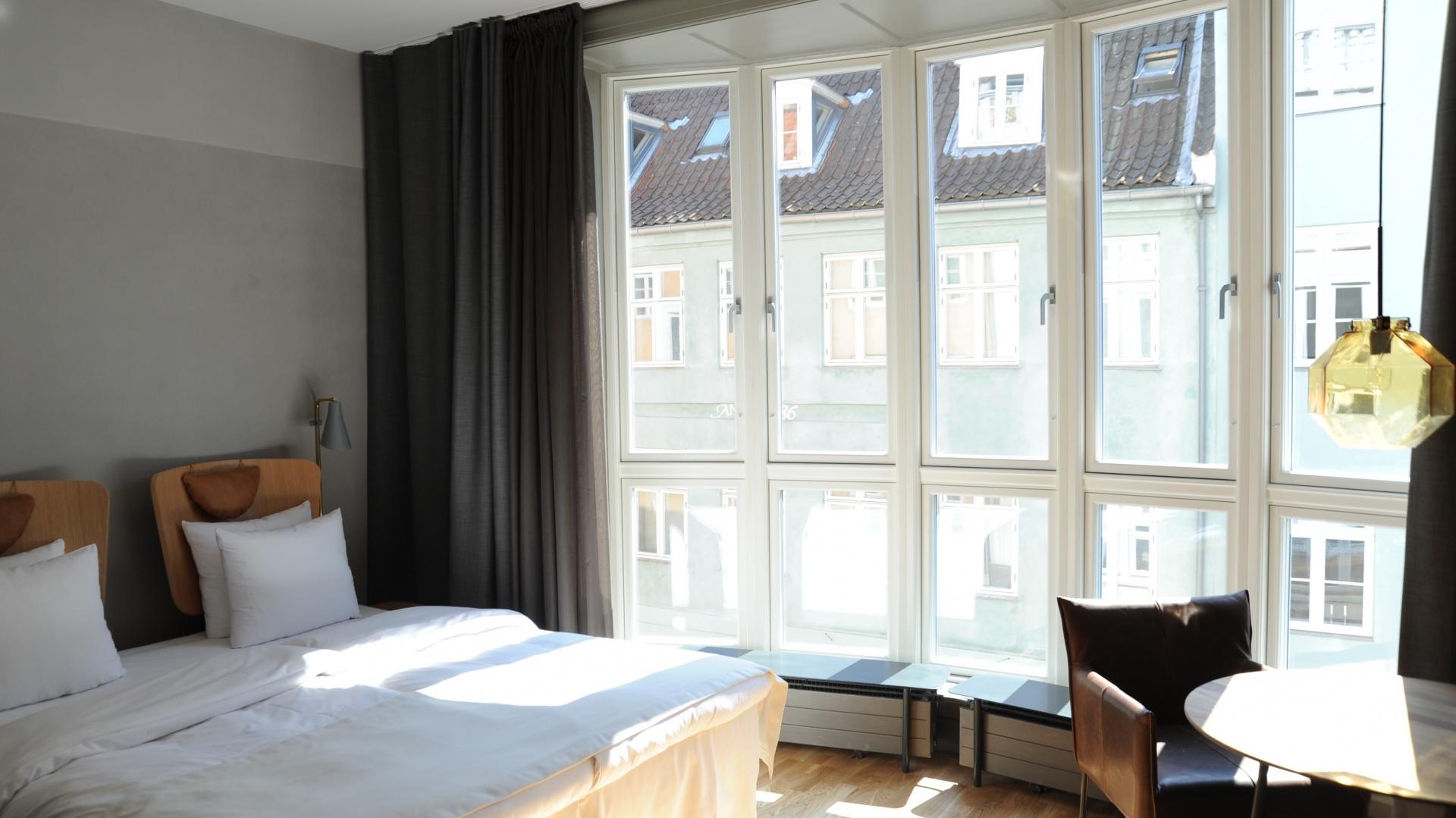 Ciężkie zasłony w oknach kontrastują z oszczędną aranżacją wnętrza. Fot. Brochner Hotels.