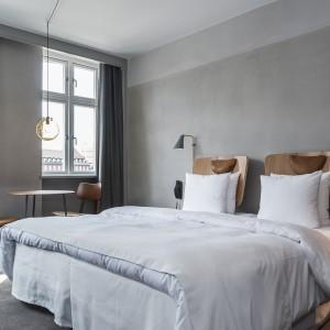 Funkcję tradycyjnych szafek nocnych przejmują niewielkie stoliki, którym nadano oryginalną, futurystyczną formę. Fot. Brochner Hotels.