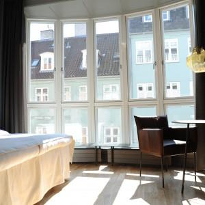 W niektórych pokojach goście mogą cieszyć się nieograniczonym dostępem dziennego światła. Wpadające do wnętrza promienie słoneczne nadają surowym formom przytulnego wyrazu. Urokliwie zaokrąglona ściana tworzy przestrzeń na wzór niewielkiej lukarny, w którą wpasowano grzejniki z siedziskiem, mogące pełnić funkcję małej ławy. Można na nich usiąść i delektować się widokami za oknem. Fot. Brochner Hotels.