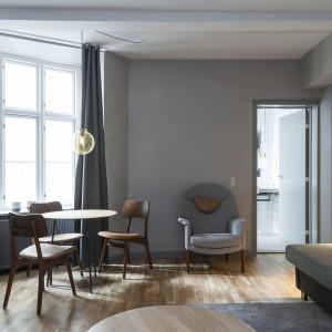 We wnętrzach pokoi hotelowych dominują zimne szarości, przełamane ciepłymi drewnianymi akcentami. Drewniana podłoga i meble, utrzymane w naturalnej kolorystyce nadają wnętrzu cieplejszego wyrazu. Fot. Brochner Hotels.