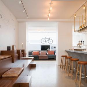 Goście hotelu mogą się zrelaksować i posilić w barze. Ten został utrzymany w cieplejszej kolorystyce niż pokoje hotelowe. Białe ściany i ciepłe drewniane akcenty nadają przestrzeni przytulnego charakteru. Fot. Brochner Hotels.