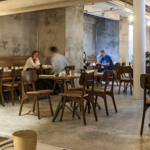 W sali śniadaniowej dominuje industrialny styl. Betonowe ściany i podłogi, odsłonięte sufity i proste drewniane meble. Całość urzeka surową elegancją. Fot. Brochner Hotels.