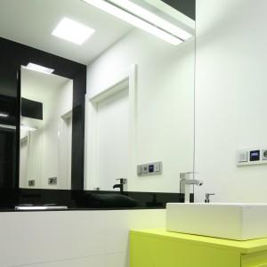 Aranżacja wnętrza oparta jest na kompozycji materiałów w czarno-białej kolorystyce. Na tym achromatycznym tle żółta szafka podumywalkowa stanowi element dodający łazience energii. Fot. Bartosz Jarosz.