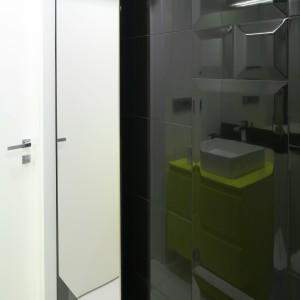 Na tle czarnych płytek świetnie prezentuje się grzejnik łazienkowy z efektem lustra. Fot. Bartosz Jarosz.