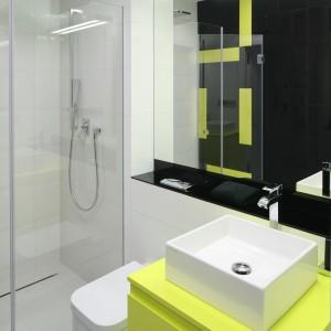 Wnękę prysznicową zdobi swobodna kompozycja żółtych płytek na czarnym tle. Pod kolor płytek dobrano także szafkę, która stanowi charakterystyczny element całego projektu. Fot. Bartosz Jarosz.