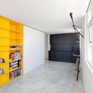 Wbudowane w ścianę półki o barwie intensywnej, żywej żółci wprowadzają energetyzujący akcent do wnętrza mieszkania. Są przy tym praktyczne i mogą pomieścić całkiem sporą biblioteczkę. Fot. Nicholas Gurney.
