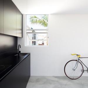 Matowa czarna kuchnia kontrastuje z otoczeniem i przyciąga wzrok. Fronty szafek o gładkiej powierzchni wpisują się w minimalistyczny styl mieszkania. Fot. Nicholas Gurney.
