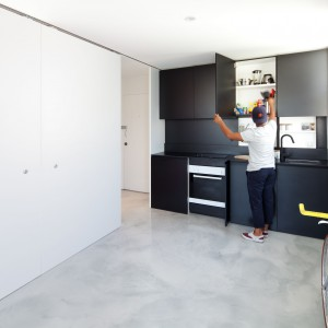 Jedynymi elementami wyposażenia, które możemy zauważyć bezpośrednio po wejściu do mieszkania są czarne meble kuchenne i czarna lampa. Za dużymi białymi drzwiami czeka jednak na nas niespodzianka... Fot. Nicolas Gurney.