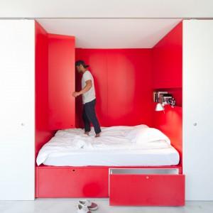 Przestrzeń do spania to także dodatkowe schowki. Pod łóżkiem znajdują się dwie duże, pojemne szuflady, a wokół łóżka umiejscowiono szafy, mogące posłużyć za garderobę. Nad głową zlokalizowaną niewielką półeczkę oraz lampkę nocną, czyli wszystko czego potrzeba do wieczornego relaksu z książką. Fot. Nicholas Gurney.