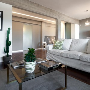 Szary, stylowy fotel jest doskonałym dodatkiem do białych sof i wspaniale prezentuje się w tym nowoczesnym wnętrzu. Fot. Archifacturing.