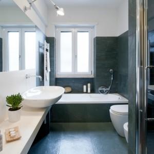 Druga łazienka to połączenie białych ścian i dużych ciemnych płytek umieszczonych zarówno na ścianach, jak i na podłodze. Fot. Archifacturing.