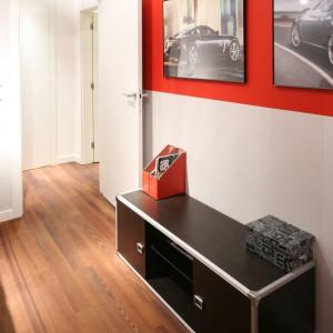 Plakaty samochodów oprawione w antyramy, zawieszone na czerwonym tle, są oryginalna dekoracją ściany pokoju nastolatka. Fot. Bartosz Jarosz.