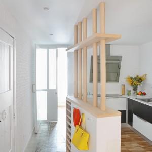 Wspólną przestrzeń kuchni z jadalnią umownie wydziela drewniana podłoga, poprowadzona wzdłuż wyspy, odgraniczającej kuchnię od przedpokoju. Fot. Asier Rua.