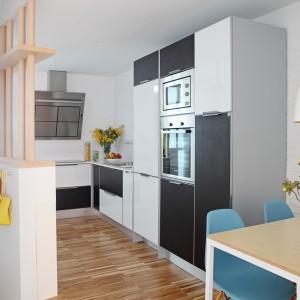 Wspólną przestrzenią, łączącą oba wnętrza jest kuchnia, utrzymana w prostej stylistyce. Biało-czarne meble z gładkimi frontami wpisują się w nowoczesny charakter pomieszczenia. Fot. Asier Rua.
