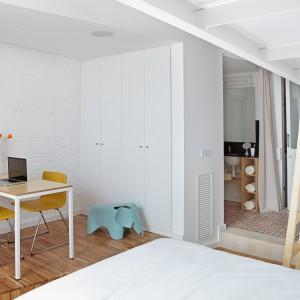 Po obu stronach kuchni zlokalizowano prywatną przestrzeń, pełniącą funkcję niezależnych mieszkań. Znajdziemy w nich sypialnię, niewielki gabinet oraz funkcjonalną łazienkę. Fot. Asier Rua.