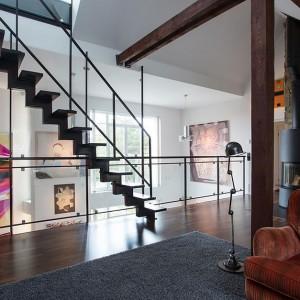 Odsłonięte belki stropowe, zamontowane pod sufitem oświetlenie reflektorowe oraz metalowe schody modułowe prowadzące na kondygnację z dostępem do tarasu, nadają mieszkaniu industrialnego charakteru. Fot. Per Jansson.
