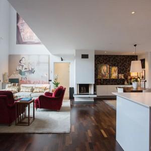 Przestrzeń dzienną mieszkania tworzy duży przestronny salon otwarty na dwie kondygnacje oraz kuchnia z jadalnią. Granicę pomiędzy salonem a przestrzenią kuchni i jadalni umownie wyznacza zlokalizowany pomiędzy nimi kominek. Fot. Per Jansson.