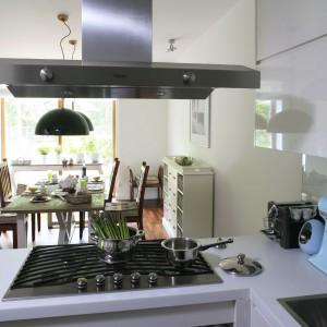 Rozwiązanie dla osób towarzyskich, lubiących gotować i rozmawiać z oczekującymi na posiłek gośćmi. Na półwyspie, wyznaczającym granicę pomiędzy jadalnią i kuchnią, zainstalowano płytkę kuchenną. Projekt: Natalia Rychtelska. Fot. Bartosz Jarosz.