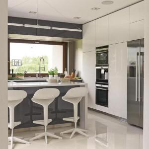 Dominującym kolorem w kuchni jest śnieżnobiała biel. Granatowa, wykończona na połysk powierzchnia frontu półwyspu komponuje się kolorystycznie z szafkami kuchennymi i przełamuje dominację bieli w pomieszczeniu, nadając mu tym samym charakteru. Fot. Dekorian.