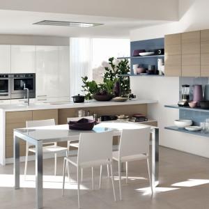 Półwysep dzieli przestrzeń kuchni i jadalni, komponując się kolorystycznie z dwiema przestrzeniami. Blat utrzymano w dominującej w kuchni bieli, podczas gdy front półwyspu współgra z podwieszonymi szafkami w jadalni. Fot. Scavolini, kolekcja Open.
