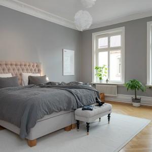 Szare ściany, drewniana podłoga, białe meble i dodatki tworzą przytulną sypialnię. Fot. Alvhem Mäkler.