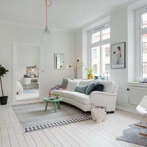 Centralnym punktem salonu jest biała kanapa, ozdobiona licznymi poduszkami. Ich kolory i wzory komponują się z dywanem, wydzielającym strefę wypoczynkową pomieszczenia. Fot. Alvhem Makleri.