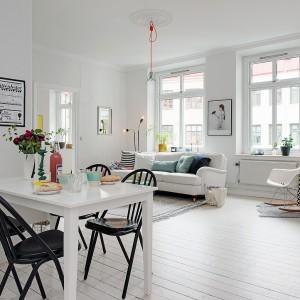 Dominującą we wnętrzu biel równoważą kolorowe tekstylia, czarne meble i czerwona cegła na jednej ze ścian. Fot. Alvhem Makleri.