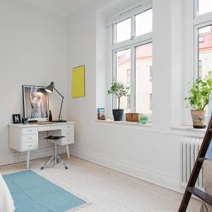 Wysokie okna w sypialni rozświetlają pięknie wnętrze. W pomieszczeniu, oprócz podwójnego łóżka, zmieszczono niewielkie biurko - przestrzeń do pracy. Fot. Alvhem Makleri.