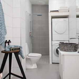 W łazience królują kolory biały i szary. Przestrzeń kabiny prysznicowej zaznaczono płytkami w ciemniejszym odcieniu szarości. Interesującym akcentem przykuwającym wzrok jest szara umywalka z kamienną okładziną. Fot. Alvhem Makleri.