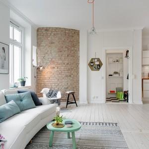Kolor do wnętrza wprowadzają tekstylia w postaci poduszek i dywanika oraz niewielki, fikuśny stolik kawowy. Fot. Alvhem Makleri.