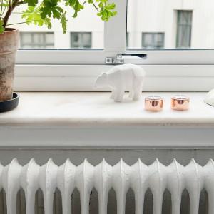Parapety w mieszkaniu wykonano z kamienia. Pięknie komponują się z białymi żeliwnymi grzejnikami. Fot. Alvhem Makleri.