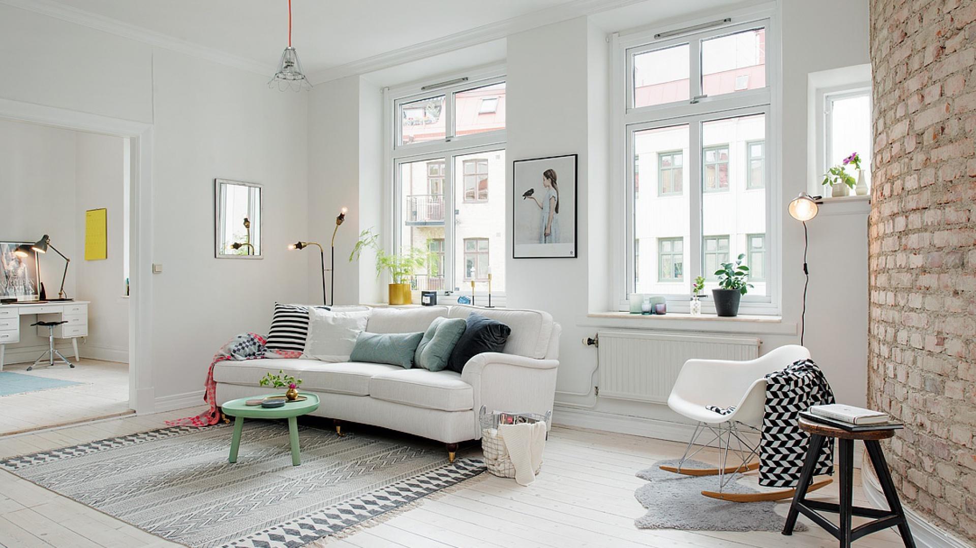 W białym salonie uwagę przyciąga ściana wykończona w całości cegłą. Wprowadza do wnętrza nieco surowego klimatu, korespondując z industrialnym oświetleniem. Fot. Alvhem Makleri.