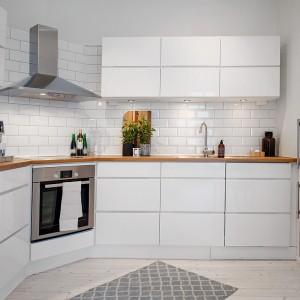 Kuchnia utrzymana jest w kolorystyce całego mieszkania, jednak panuje w niej nowoczesny styl. Minimalistyczne gładkie fronty szafek kontrastują ze starą drewnianą podłogą i przytulnym dywanikiem. Fot. Alvhem Makleri.
