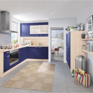 Granatowe fronty mebli kuchennych na tle jasnego odcieniu drewna tworzą kompozycję bliską kontrastowi i przykuwają wzrok. Kolorystycznie komponują się z mozaiką nad kuchenką. Fot. Pino, meble z programu PN 100.