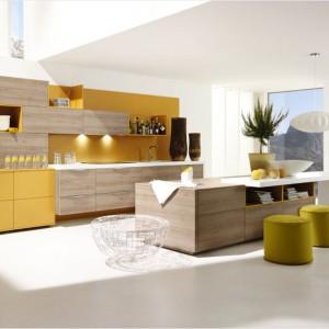 Przytulnie i ciepło. Jesienny złoty kolor nad blatem kuchennym, frontach części szafek oraz w postaci przytulnych puf tworzą wraz z naturalnym odcieniem drewna przytulny klimat w tej przestronnej kuchni. Fot. Alno, meble z programu 252 Alnoplan.