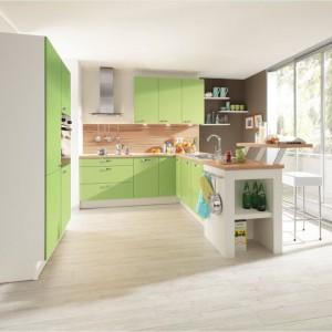 Kuchnia w smakowitym odcieniu awokado. Zielone fronty szafek tworzą spójną wizualnie całość z naturalnym odcieniem drewna i eksponującą je bielą. Fot. Pino, meble z programu PN 160.