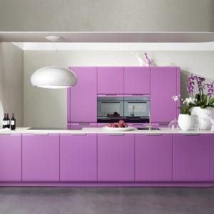 Urokliwa kuchnia w której szarości stały się bazą do wyeksponowania mebli kuchennych w kolorze fioletu orchidei. Kompozycję barw uzupełnił biały blat kuchenny. Fot. Leicht, meble z kolekcji Onda.