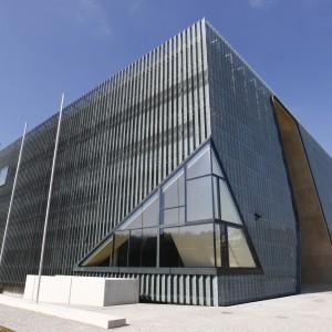 Budynek Muzeum został zaprojektowany na planie kwadratu – ma postać prostopadłościanu o szklanych ścianach. Jego elewacja jest bowiem wzniesiona ze szklanych paneli i miedzianej siatki. Konstrukcja ścian opiera się na stalowych rurach powleczonych betonem. Fot. Muzeum Historii Żydów Polskich Polin.