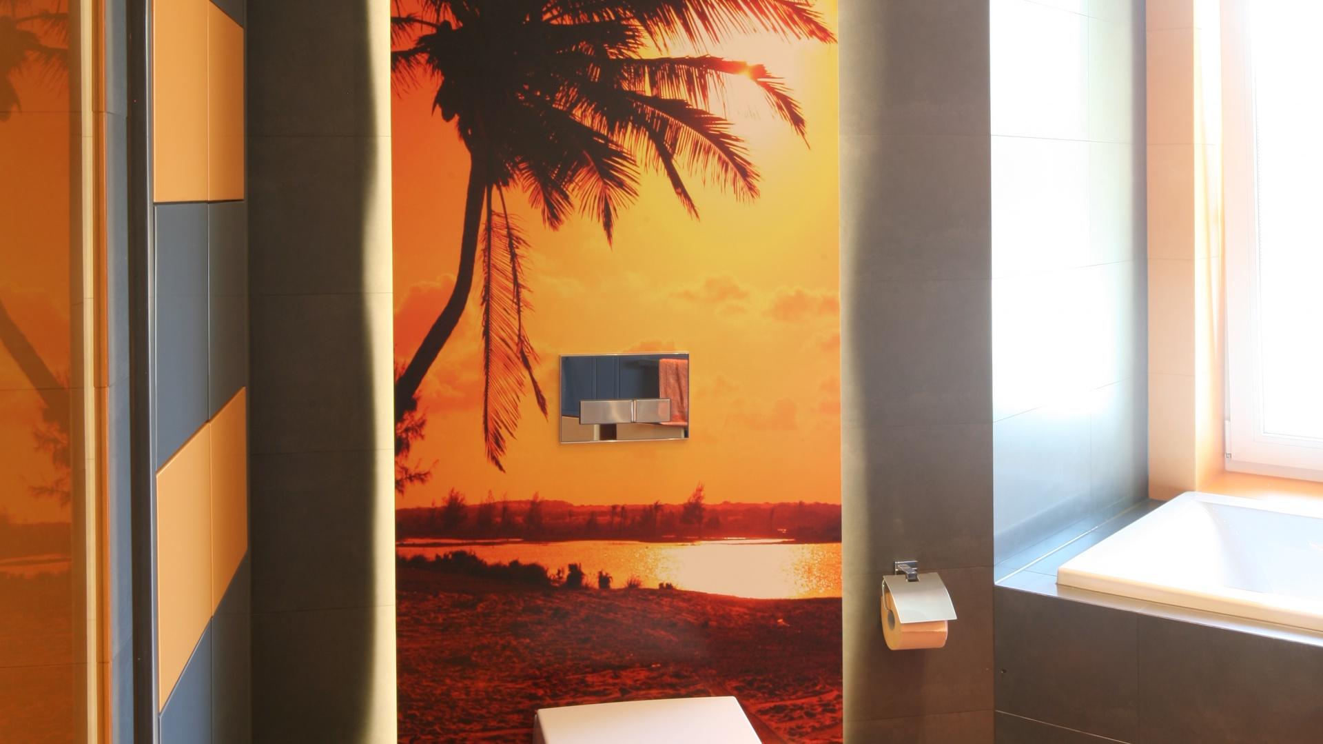 Do łazienki dla nastoletnich chłopców wybrano energetyczny pomarańcz zestawiony z uniwersalnymi szarościami. Do tej kolorystyki dopasowano także fototapetę: z widokiem egzotycznej plaży. Projekt: Monika i Adam Bronikowscy. Fot. Bartosz Jarosz.