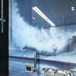 Nadrukowana na szkle fotografia z motywem wody w błękitnym kolorze świetnie zdobi łazienkę i nadaje wnętrzu oryginalny charakter. Projekt: Monika i Adam Bronikowscy. Fot. Bartosz Jarosz.