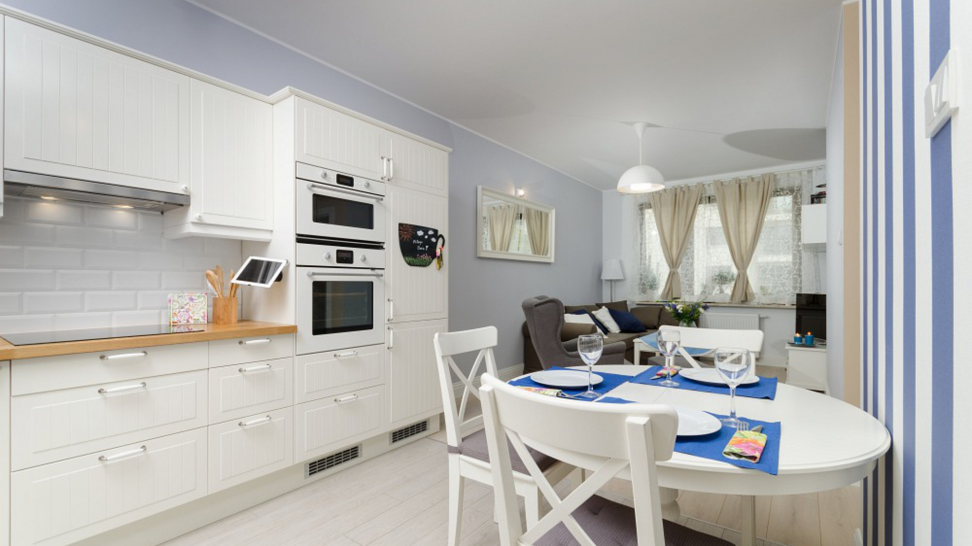 Kuchnia z jadalnią i salonem tworzą wspólną otwartą przestrzeń. Dominują w niej chłodne odcienie bieli, szarości i błękitów. Cieplejszym akcentem są drewniany blat i beżowe zasłony w oknach. Fot. Decoroom.
