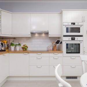 Kuchnię utrzymano w klasycznym stylu, z domieszką skandynawskiego klimatu. Biała glazura nad blatem imituje tradycyjne kafle kuchenne. Kontrastującym akcentem jest ukłon w stronę nowych technologii - zamontowany nad blatem kuchennym uchwyt na iPoda. Fot. Decoroom.
