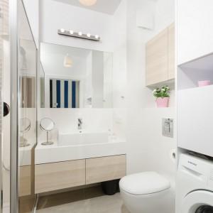 Jasna łazienka została wykończona w nowoczesnym stylu. Płaskie fronty szafek, podwieszane wc i prostokątna umywalka wpisują się we współczesną stylistykę. Jasne odcienie drewna i bieli optycznie powiększają wnętrze. Kolor do pomieszczenia wprowadzają tapeta na ścianie i różowe dodatki. Fot. Decoroom.