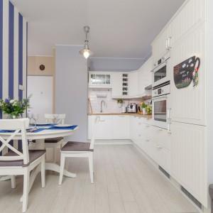 Tapeta w żywym odcieniu indygo kolorystycznie komponuje się z podkładkami na stole i ożywia wnętrze. Pełni także praktyczną funkcję w długim pomieszczeniu, dodając mu optycznie kilku centymetrów wysokości. Fot. Decoroom.