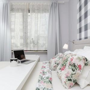 Stonowane szarości i biele nadają sypialni spokojnego charakteru. Tekstylia z motywem kwiatowym ożywiają wnętrze. Fot. Decoroom.