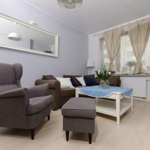 Niewielki metraż mieszkania optycznie powiększono jasną podłogą i meblami w kolorze białym. Dodatkowym trikiem optycznym jest zamieszczone na ścianie długie lustro. Fot. Decoroom.