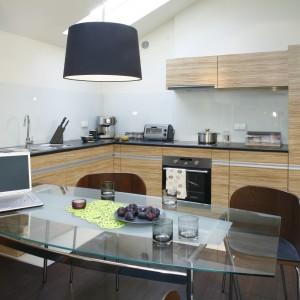 Duży stół, dzięki temu, że jest ze szkła, nie zmniejsza wizualnie kuchni. To wygodne miejsce na posiłki, także w większym gronie. Projekt: Katarzyna Merta-Korzniakow. Fot. Monika Filipiuk-Obałek.