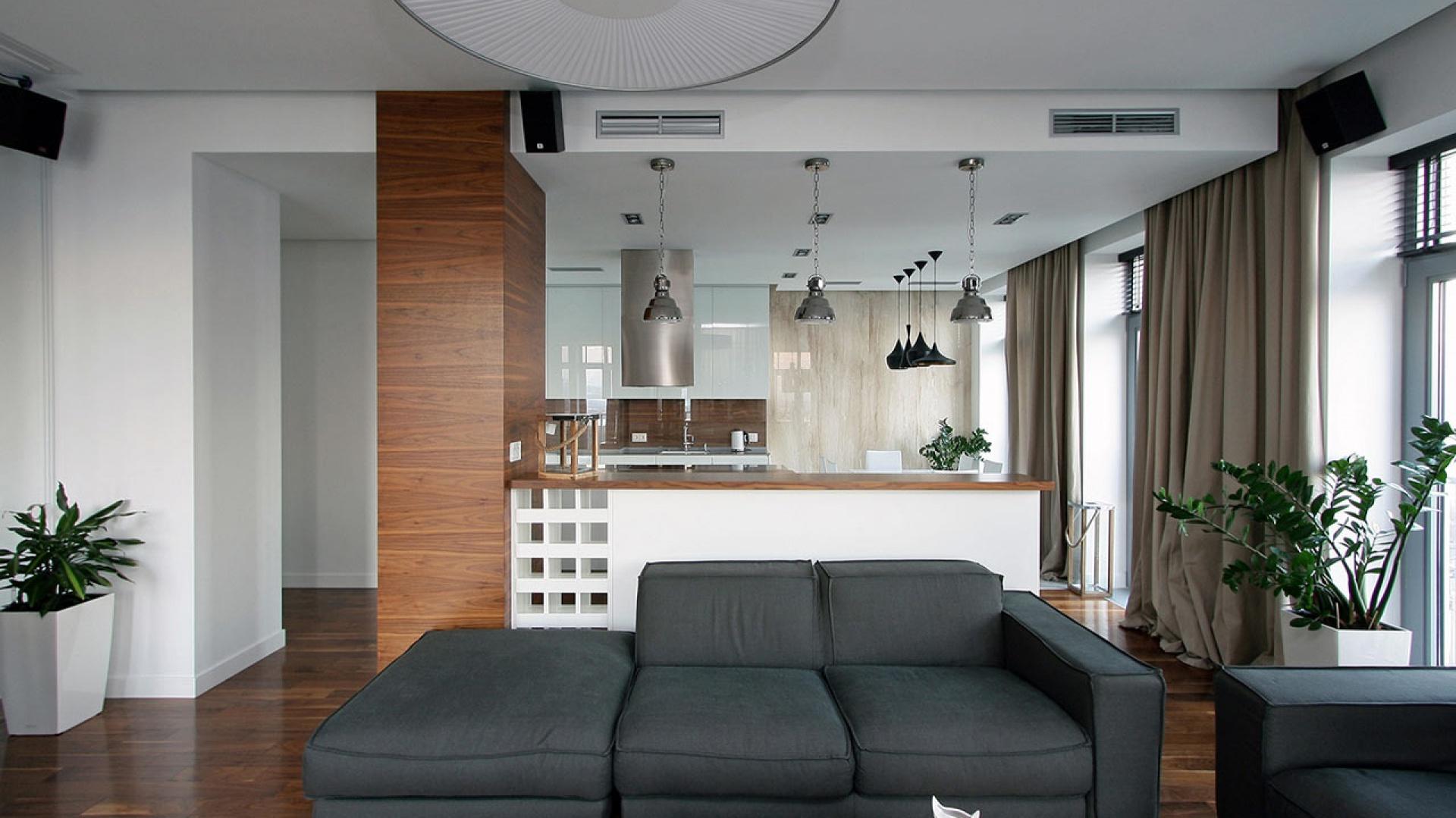 Szare sofy doskonale prezentują się na tle białych ścian i świetnie pasują do drewnianej podłogi. Fot. Svoya studio.