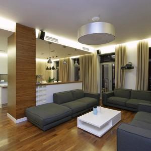 Salon jest bardzo duży, dlatego zmieściły się w nim aż trzy duże, szare sofy. Fot. Svoya studio.